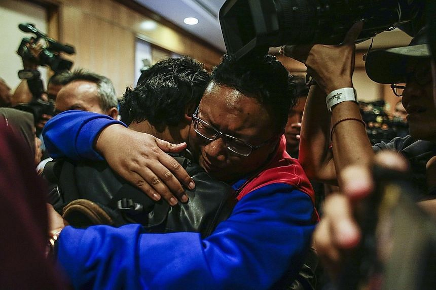 One of the nine returning Malaysian nationals hugging his relative in Kuala Lumpur yesterday.