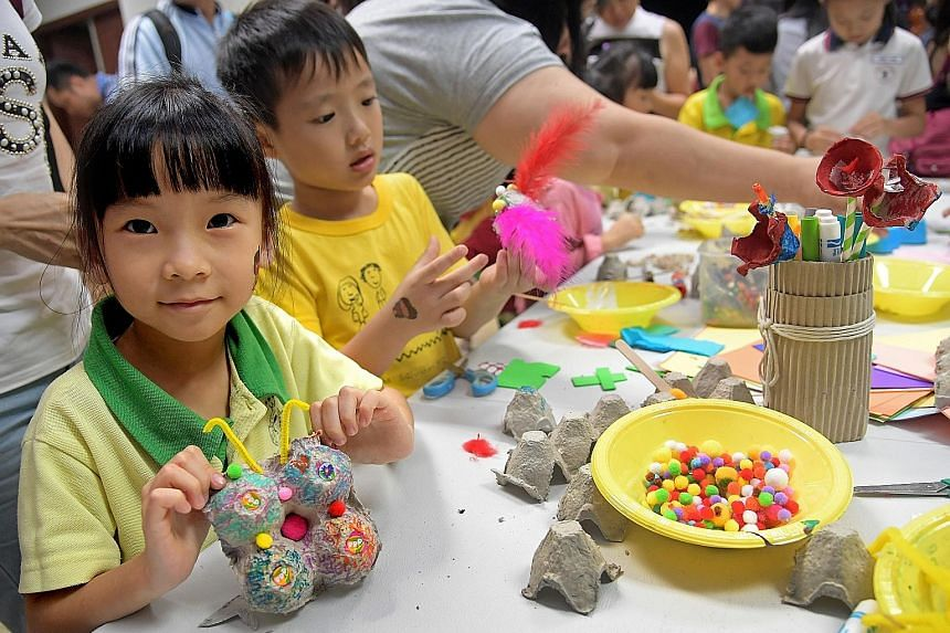 Yu Zi Xing, six, with a butterfly she made from recycled materials at the Recycling Carnival yesterday, which featured games and crafts stations made out of recycled materials.