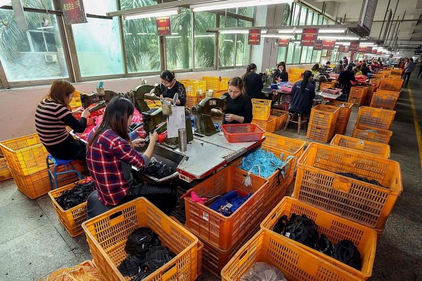 Workers at a shoe factory in China, which enjoys the largest trade surplus with the United States. However, in Beijing yesterday, officials sought to downplay trade tensions with Washington.