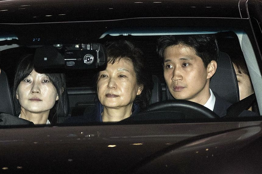 Ms Park (centre) being driven from the Central Prosecutors' Office in Seoul to the detention centre yesterday.