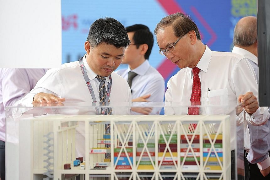 Mr Koh (left), Yang Kee Group chief executive, and Mr Ted Tan, deputy chief executive of Spring Singapore, with a model of Yang Kee's Tuas logistics hub, a joint development with Logos Southeast Asia.