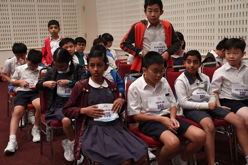 Pupils at Spelling Bee semi-final at SPH Auditorium adjusting their bibs before the finals start.