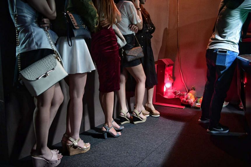 Hostesses at a KTV bar on Sam Leong Road line up during a police raid in the early hours in the early hours of Saturday (April 1).