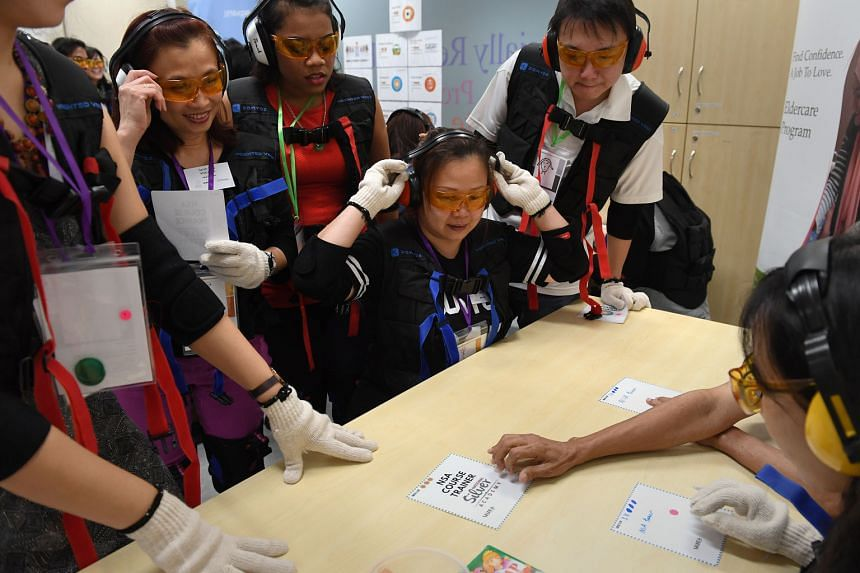 Madam Wendy Teo adjusting her ear mufflers at the workshop, where she and her fellow participants donned a heavy vest, glasses and mufflers to simulate old age. Workshops like this are part of the Eldercare Program, which prepares low-income women and sin