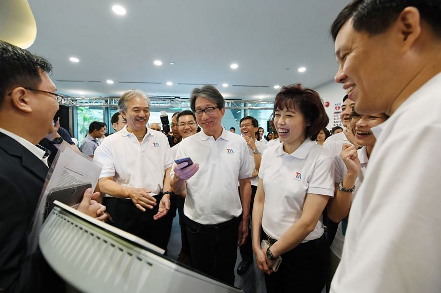 Minister Lim receiving an SMS on his cellphone giving him a queue number for a walk-in appointment at the Tripartite Alliance for Dispute Management yesterday. With him are (from left) Snef president Robert Yap, NTUC president Mary Liew and Minister