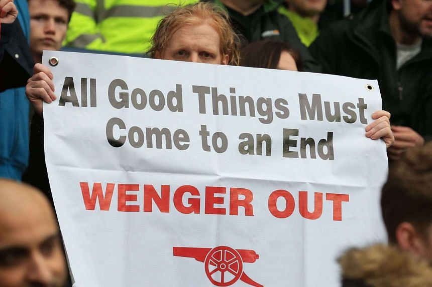 Arsenal fans hold up anti-Arsene Wenger signs after the EPL match against West Bromwich Albion on March 18, 2017.