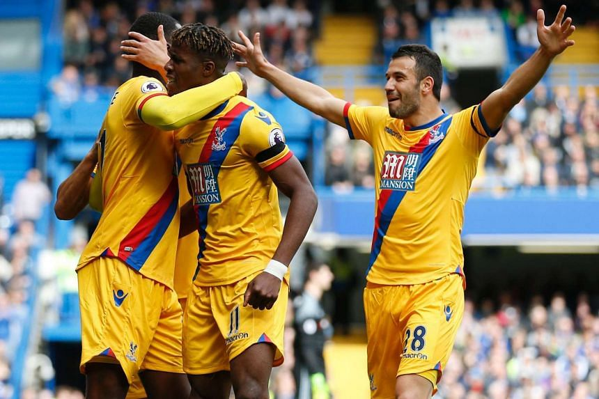 Crystal Palace's Zaire-born Belgian striker Christian Benteke (left) celebrates with teammates after scoring their second goal.