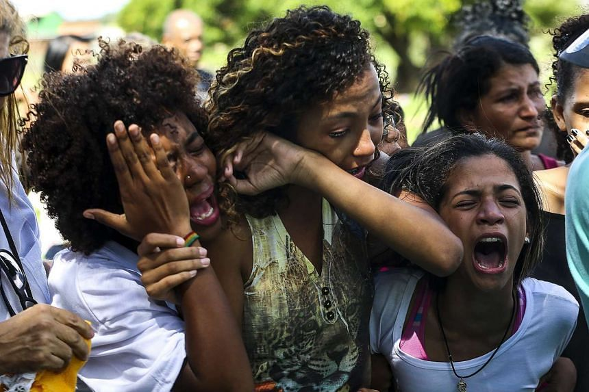 Relatives and friends of María Eduarda Alves mourn during her funeral.