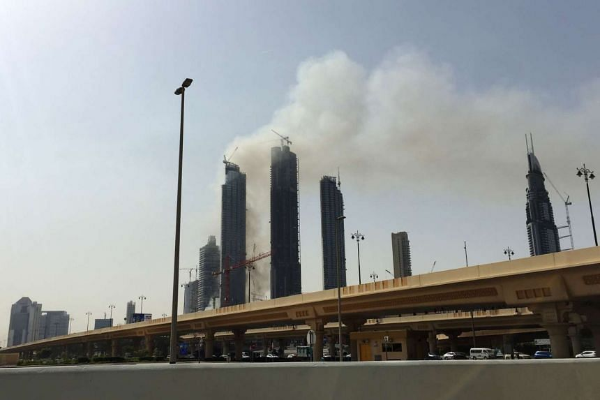 Smoke is seen billowing from an under-construction residential complex near the Dubai Mall and Burj Khalifa in Dubai, on April 2, 2017.