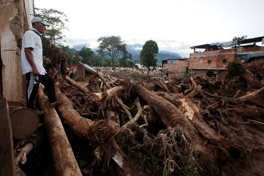 A man looks at a destroyed area after heavy rains caused several rivers to overflow, pushing sediment and rocks into buildings and roads in Mocoa on April 1, 2017.