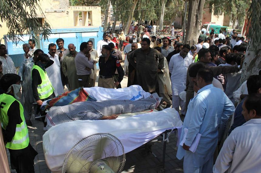 Rescue workers and security officials gather around the bodies of the disciples who were killed in Sargodha, Pakistan.