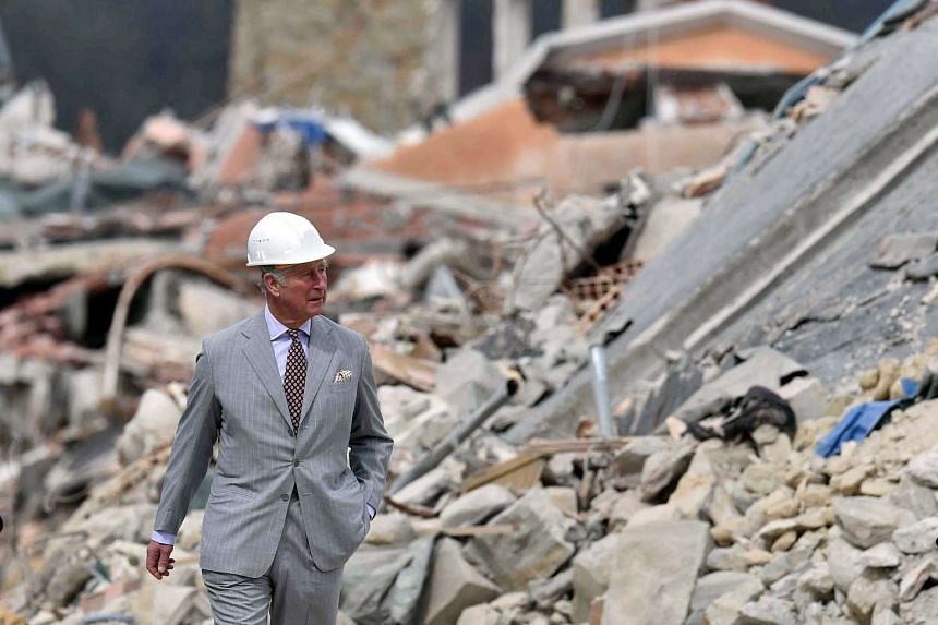 Prince Charles walking through the town of Amatrice, which was levelled after an earthquake last year.