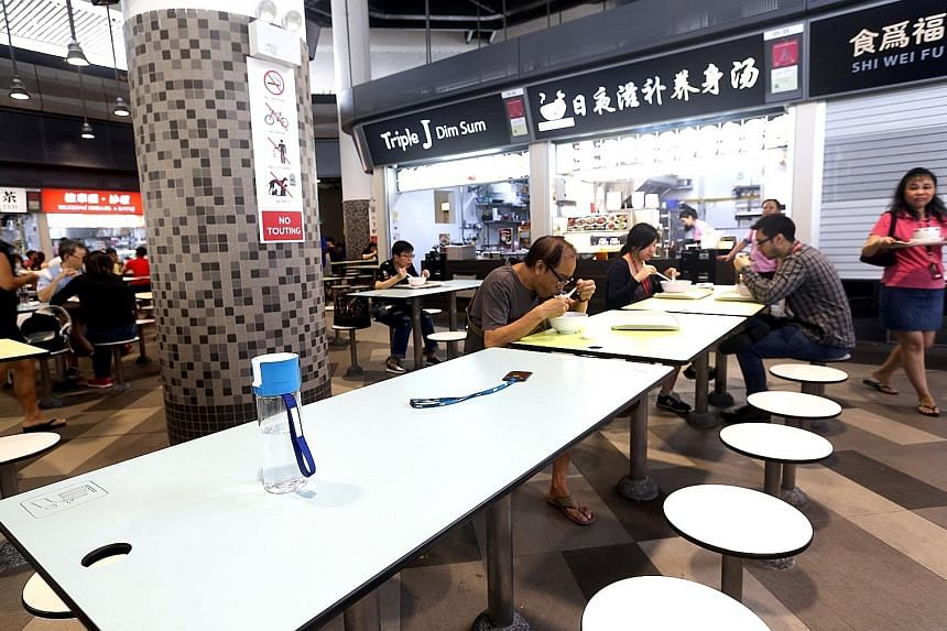 """Above, from left: Diners chope seats with items like umbrellas, work passes and water bottles. These pictures were taken at the food centre at Our Tampines Hub which, ironically, has introduced a set of """"house rules"""" on seat-choping."""
