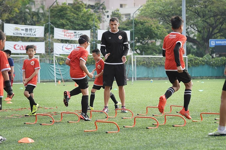 Former national striker Aleksandar Duric, the principal of the ActiveSG football academy, offering encouragement to youngsters at Jurong East yesterday. A year since it opened its doors, the academy has 716 pupils on its books.