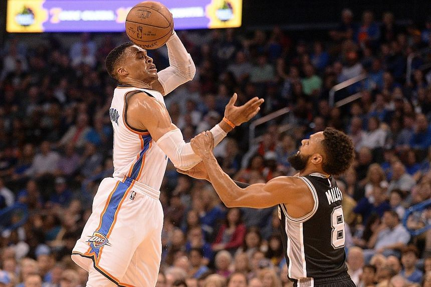 Coming to grips with the challenge of keeping Russell Westbrook at bay, Patty Mills of the San Antonio Spurs fouls the Oklahoma City Thunder guard during the Spurs' 100-95 victory.