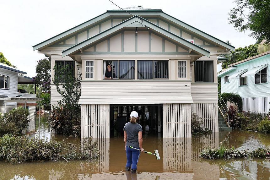 Where to begin the cleanup? The couple are among residents in the town of Lismore, New South Wales, yesterday who are returning to their homes as the flood water in their area recedes. Tens of thousands of people have been evacuated from a string of