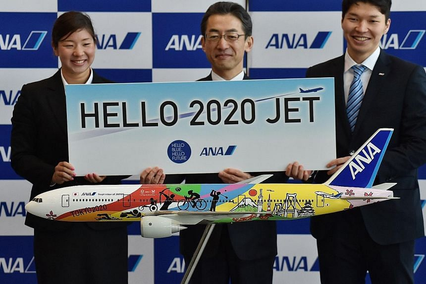 All Nippon Airways' (ANA) new president Yuji Hirako with new employees and a model of an ANA aircraft in special livery for the Tokyo 2020 Olympic and Paralympic Games, after the company's welcome ceremony for new employees, at a hangar in Tokyo's Ha