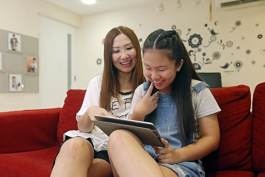 Chervone Wuan, 12, using a tablet under the supervision of her mother Michelle Low, 42. The increased usage of such devices among kids can expose them to online dangers.