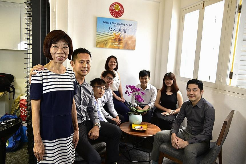 Ms Sim Lay Koon (left), now a senior account associate at consultancy firm Bridge 2 Biz Consulting, with (from left) managing director Henry Ong and colleagues Tan Zheng Bang, Chang Si Jie, Lek Mei Ting, Sean Tan, Woan Yng and Ryan Chan. Ms Sim's exp