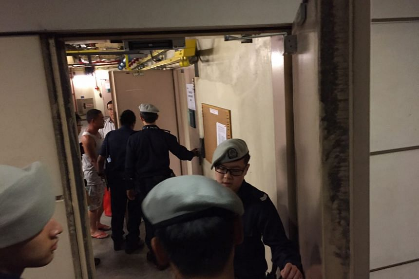 A man being led away by the police into the staff area at Hougang MRT station.