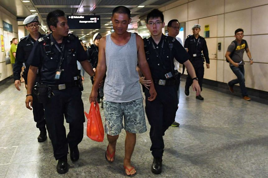 The man being led away by the police into the staff area at Hougang MRT station.