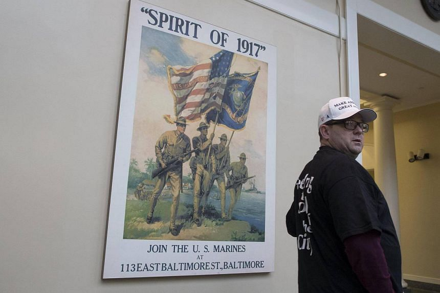A visitor passes by a replica of a World War I recruitment poster, at the World War I centennial commemorative exhibit at Arlington National Cemetery.