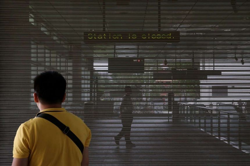 An SBS Transit staff member is seen behind shutters after Hougang MRT Station was closed temporarily due to the security incident on April 2, 2017.