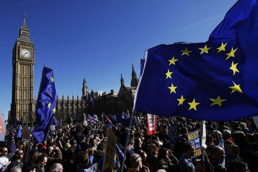 Protesters carry European Union (EU) flags in front of Big Ben during a Unite for Europe march to protest Brexit in central London, on March 25, 2017.