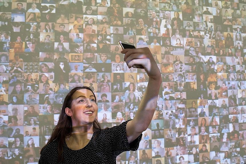 A gallery assistant in front of an audio-visual installation, titled Hello World! (2008), by American artist Christopher Baker at a press preview for the exhibition From Selfie To Self-Expression at London's Saatchi Gallery.