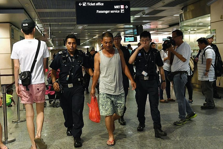 Police escorting the man who deliberately left his bag at the platform of Hougang MRT Station yesterday while he ran an errand.
