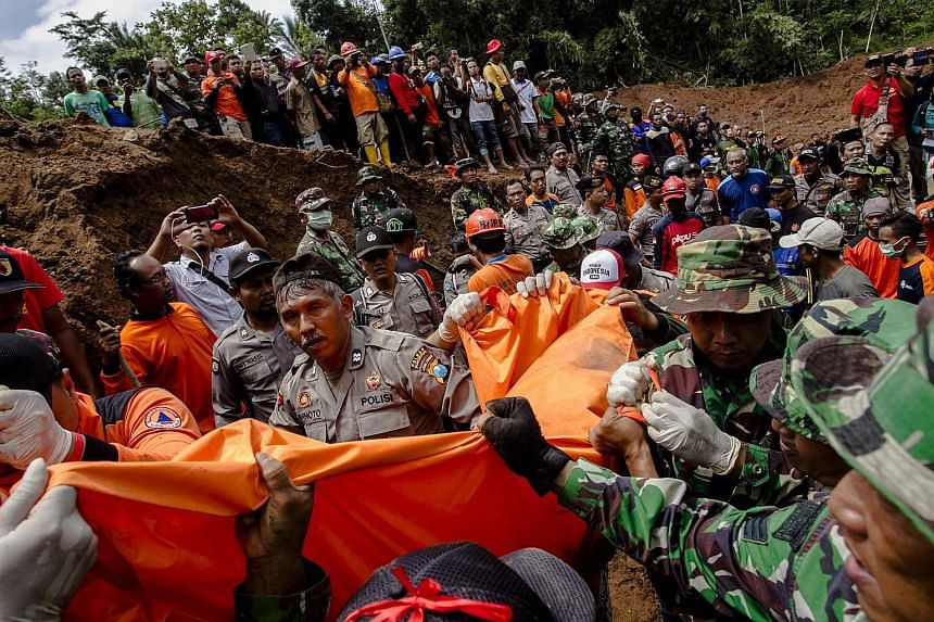Indonesian soldiers and rescuers yesterday removing the body of a victim in Banaran, a village in Ponorogo district, East Java, which was hit by a landslide the day before.