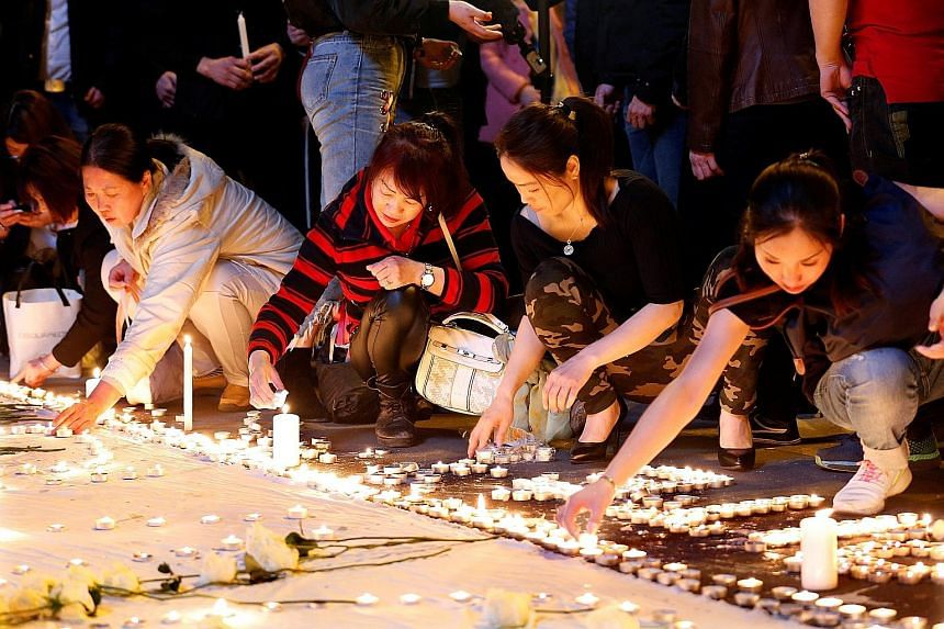 Members of the Chinese community in France lighting candles during a protest in Paris last Thursday, after a Chinese man was shot dead by police at his Paris home late last month.