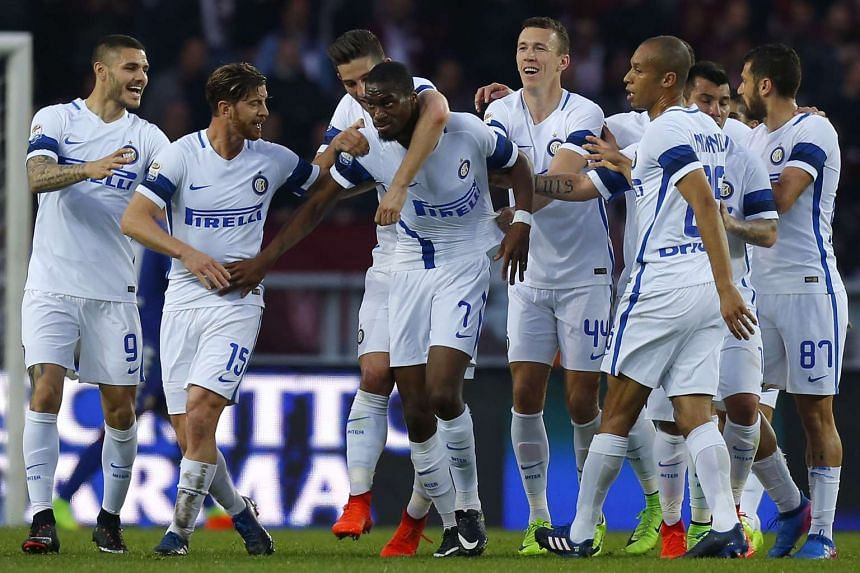 Inter Milan's French midfielder Geoffrey Kondogbia (centre) celebrating with teammates after scoring during the Italian Serie A football match Torino versus Inter Milan, on March 18, 2017