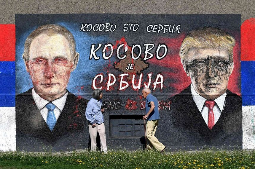 "People walk past a wall depicting Russian President Vladimir Putin (left) and US President Donald Trump with a message reading ""Kosovo is Serbia"" in Belgrade on April 2, 2017."