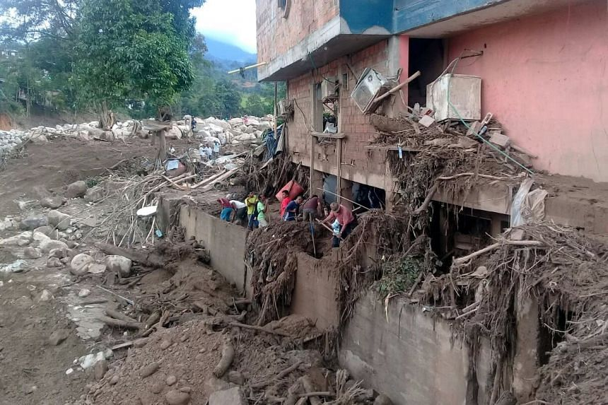 Inhabitants clear the wreckage left by a mudslide in Mocoa, Colombia on April 2, 2017.