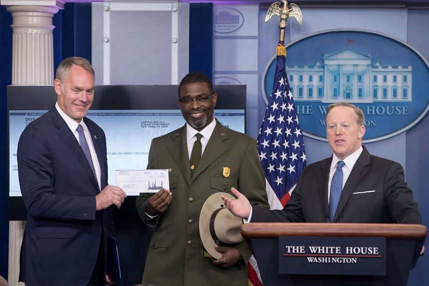 White House Press Secretary Sean Spicer gestures after handing over a check of funds donated by President Donald Trump to US Interior Secretary Ryan Zinke (left) and Harpers Ferry National Historical Park superintendent Tyrone Brandyburg (centre).