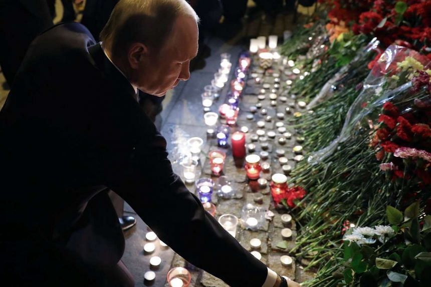 Russian President Vladimir Putin (centre) lays flowers outside Tekhnologicheskiy Institut metro station after an explosion took place earlier in the day.