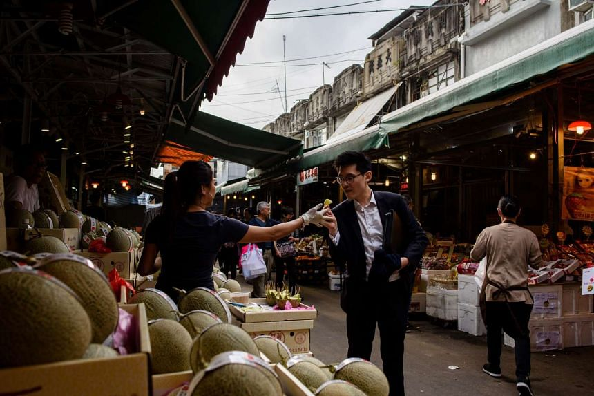 A customer is offered a slice of premium Japanese melon, which costs US$15 (S$21), at the Yau Ma Tei fruit market in the Kowloon district of Hong Kong.