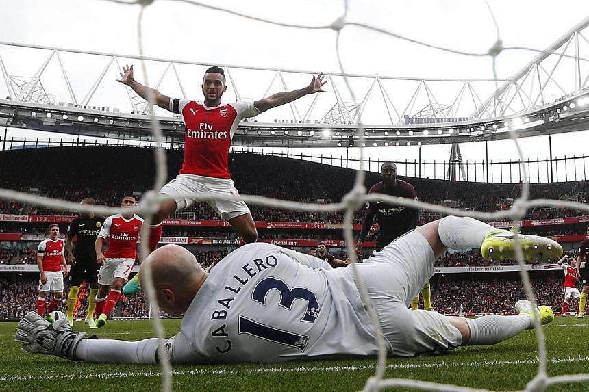 (Top) Arsenal forward Theo Walcott celebrating following team-mate Shkodran Mustafi's 53rd-minute header and equaliser past City goalkeeper Willy Caballero. (Above) Fans making their point as the protests against Arsenal manager Arsene Wenger get mor