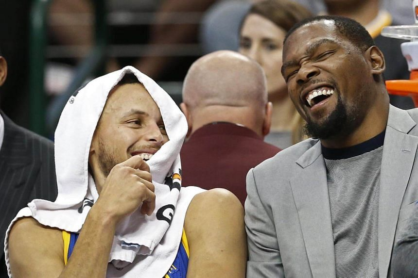 Injured Golden State Warriors forward Kevin Durant (right) joking with teammate Stephen Curry on the bench during the NBA match against the Dallas Mavericks on March 21, 2017.