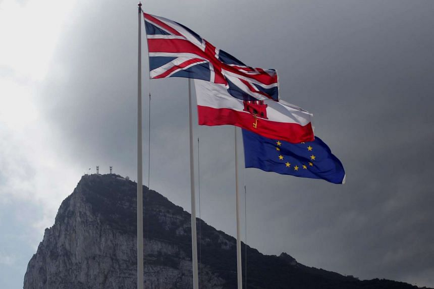The Union Jack (left), Gibraltarian flag (centre) and European Union flag are seen flying in front of the Rock in Gibraltar on April 3, 2017.