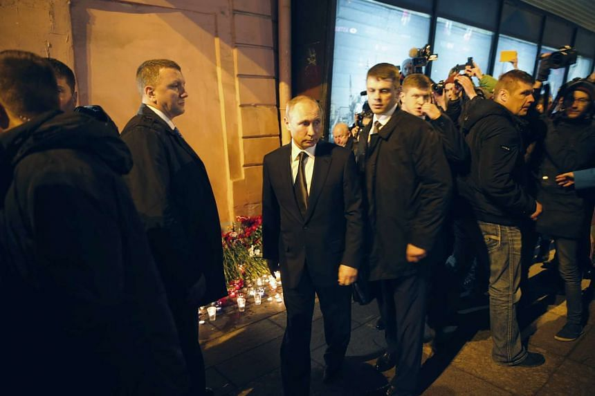 Russian President Vladimir Putin (centre) lays flowers outside the metro station rocked by the blast on April 3, 2017.