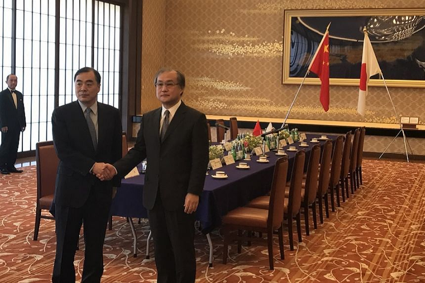 Chinese assistant foreign minister Kong Xuanyou (left)  with Japanese deputy foreign minister for political affairs Takeo Akiba (right) before their meeting at the Iikura Guest House in Tokyo on April 4, 2017.