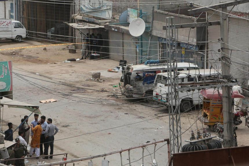 Security officials gather at the site of the explosion, near the vehicles used in the census.