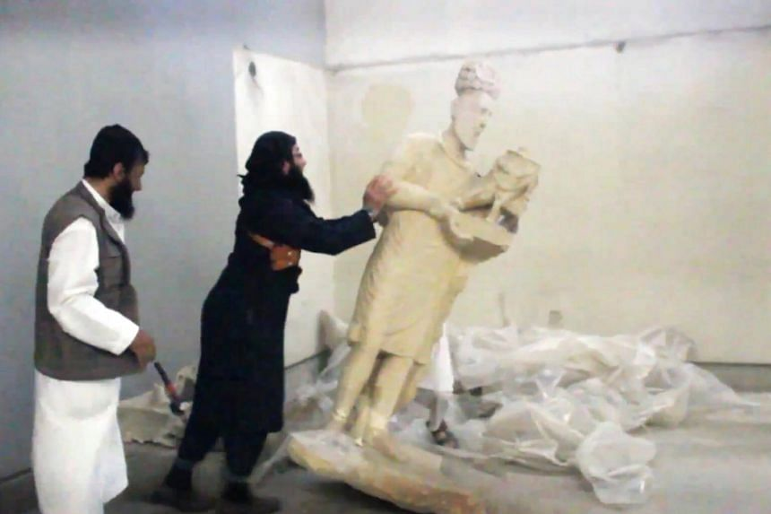 This screengrab taken off a video allegedly shows an ISIS militant pushing a statue inside the Mosul Museum.
