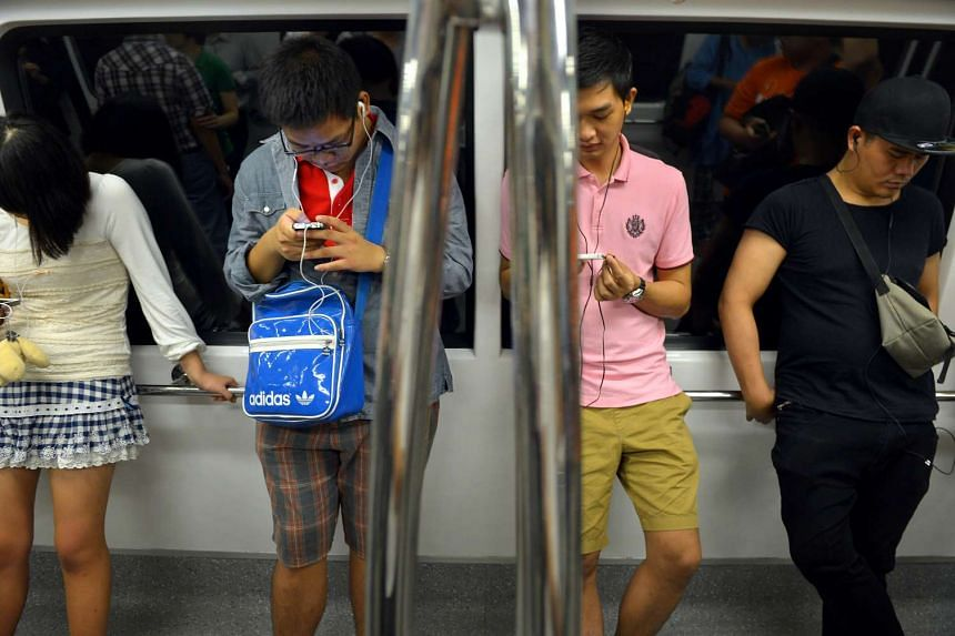 People using their mobile phones onboard a train.