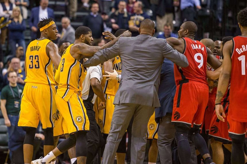 Players from the Indiana Pacers (in yellow) and Toronto Raptors get into a scuffle after Pacers guard Lance Stephenson scored a layup in the closing seconds of the game.