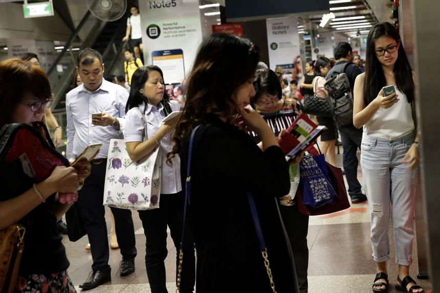 Commuters on their mobile phones while waiting for the train at City Hall MRT Station.