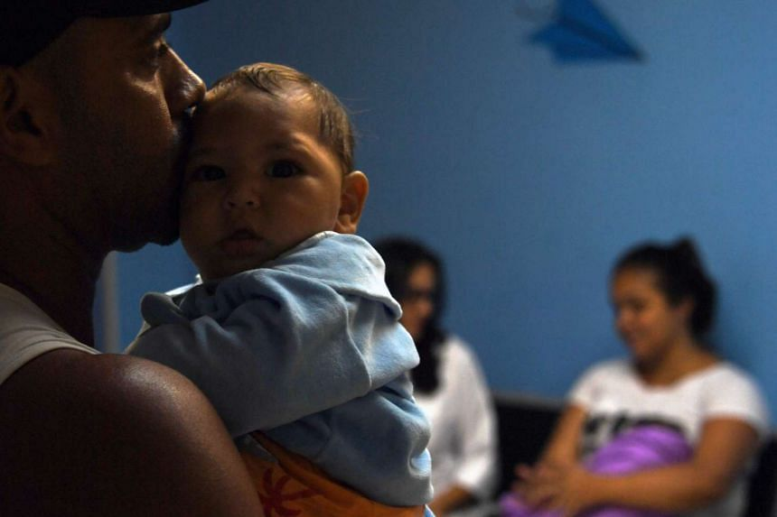 Paulo Sergio holds his six-month-old baby Arthur Meneses as they wait for medical exams in Brazil. Arthur's mother was infected with the Zika virus while pregnant.