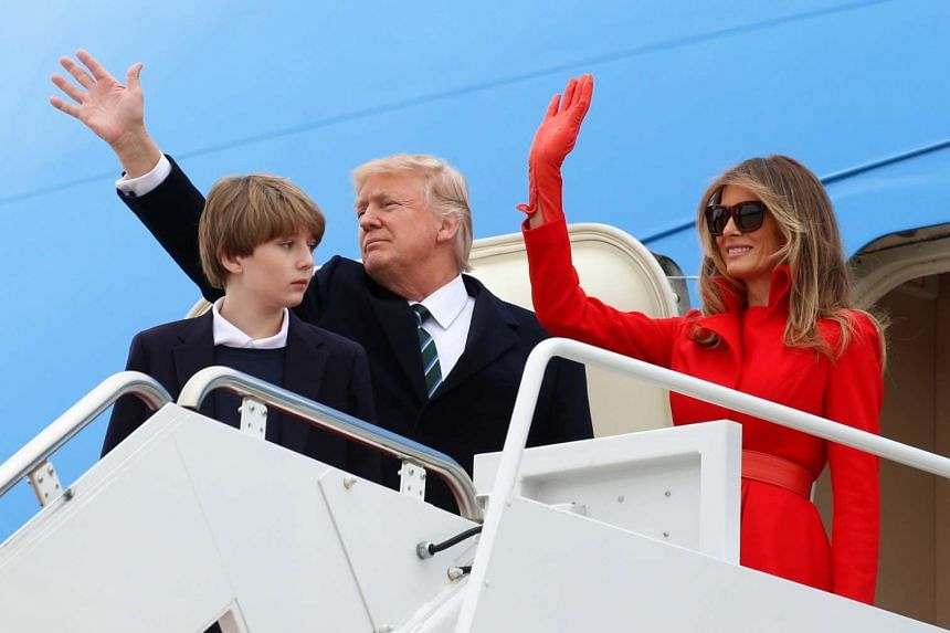 US President Donald Trump, his wife Melania and son Barron wave as they Board Air Force One for Florida, March 17, 2017.